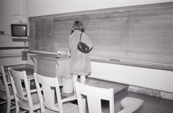 Woman Stands in Empty Classroom with Note